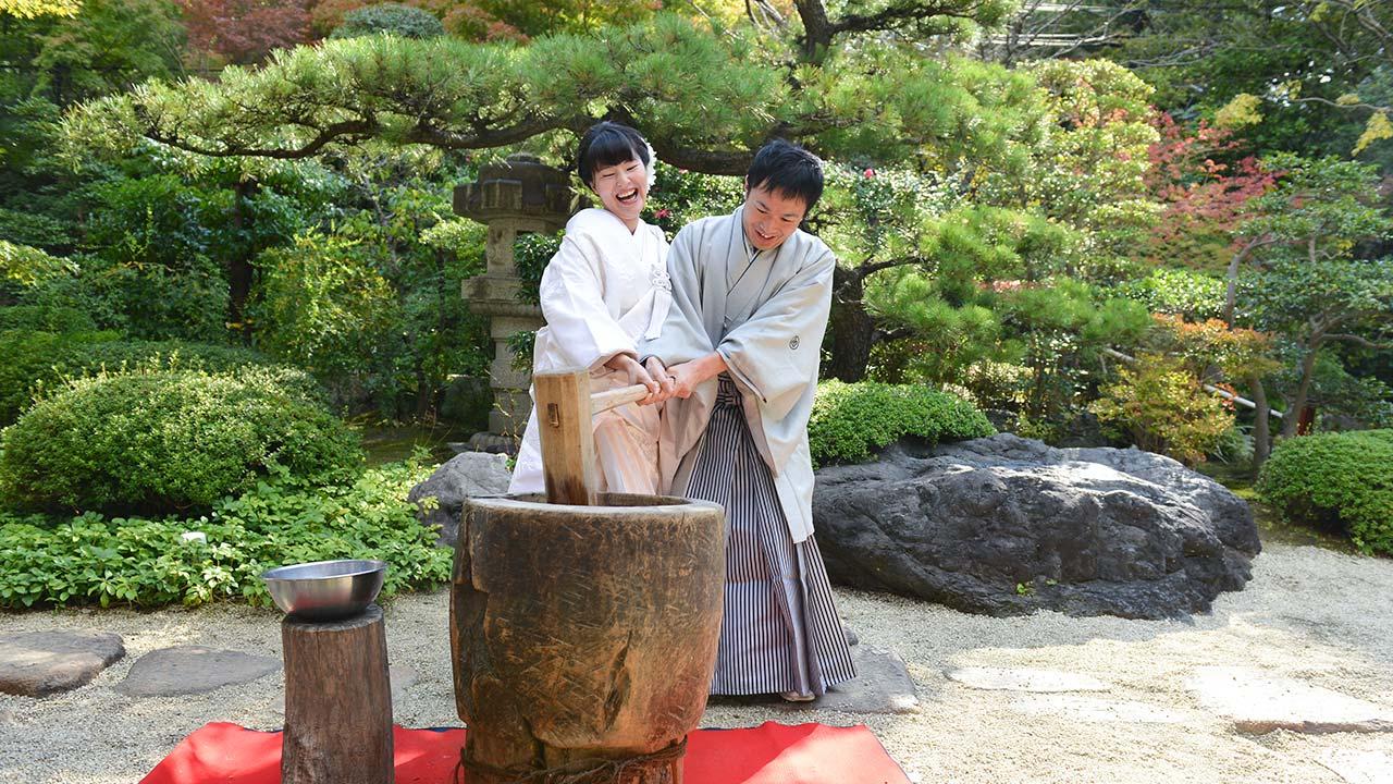 立派な日本庭園で餅つきを楽しむ新郎新婦