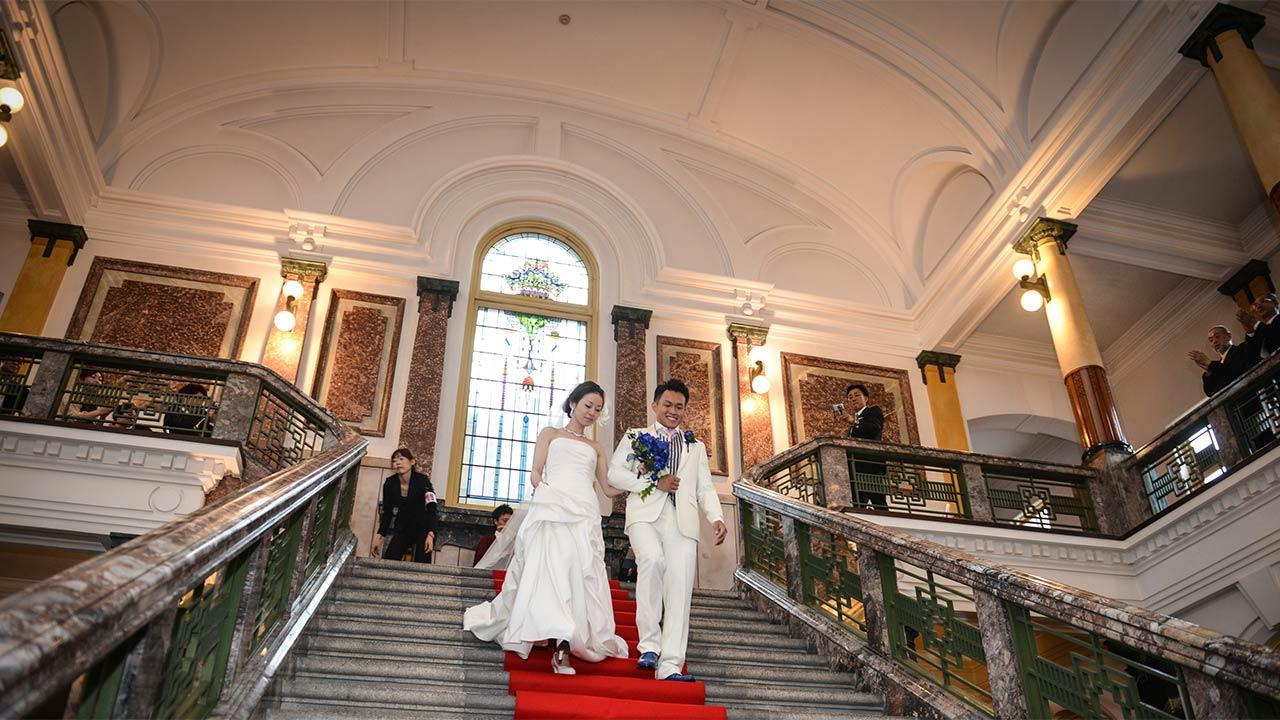 手をつないで立派な大階段を下りる新郎と新婦