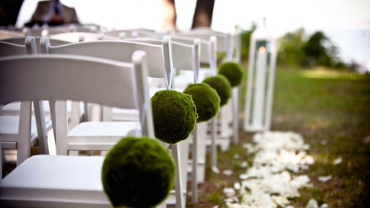 結婚式のセレモニーのために緑の芝生の上に並べられた椅子