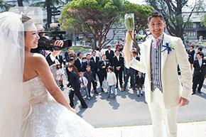 結婚式場の前で微笑む新郎新婦